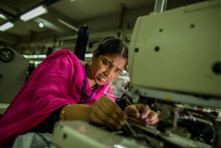 Shahara, a garment worker in Bangladesh, stitches buttons on blazers at her workstation in a garments factory in Gazipur, Dhaka. / Josh Estey, USAID