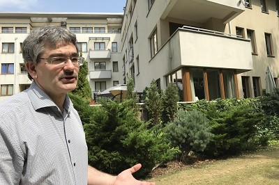 A man in front of apartment buildings