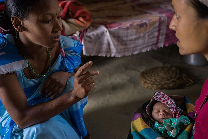 A health worker talks to a new mother holding her baby.