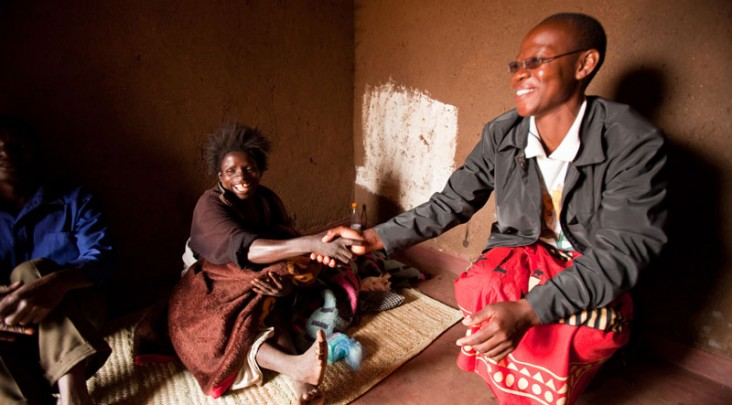 A health worker shakes hands with an AIDS patient in their home.