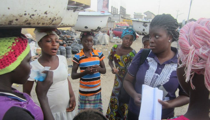 Photograph of a group of women in a market, discussing health issues. Photo credit: Yakuba Yusuf/Project HOPE
