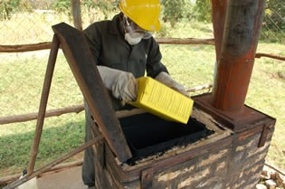 A waste handler loads a safety box with infectious sharps waste into an incinerator for final disposal.