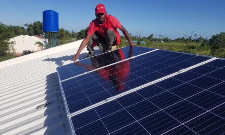 A SolarWorks! employee installing a PV panel in Sofala, Mozambique