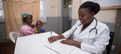 A nurse takes notes while a mother and her child site nearby.