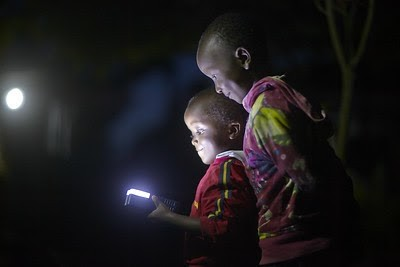Two children look at a flashlight