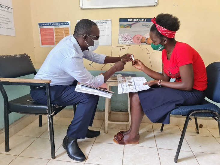 Madiang' sensitizes a young woman on the use of HIV self-testing at a safe space in Kisumu County.
