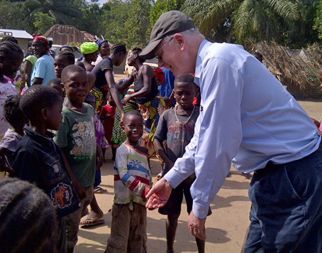 USAID Global Water Coordinator Christian Holmes congratulating children in forest community in Liberia