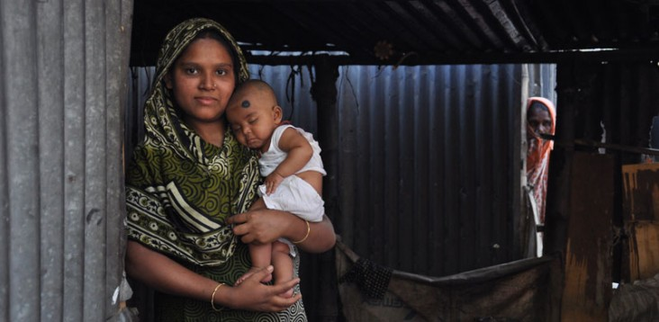 A mother holds her child in the doorway of their home.