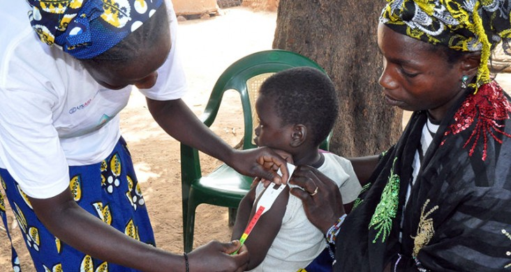 Photo of a child being measured by a community health worker