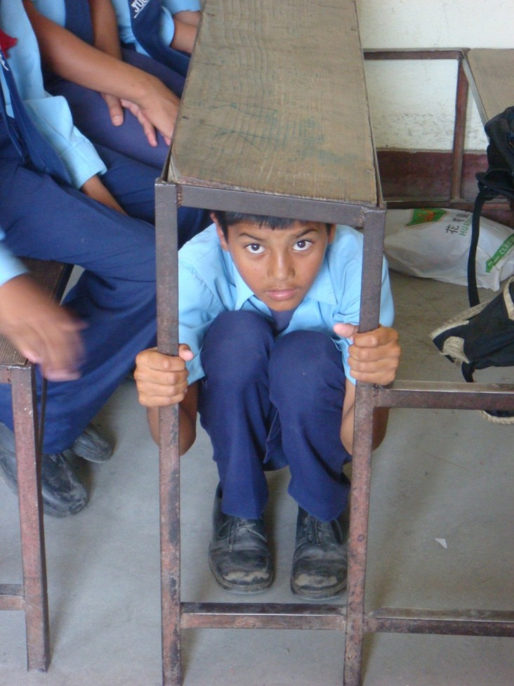 This student in Nepal demonstrates the appropriate reaction in the event of an earthquake.
