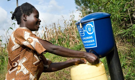 Dispensing chlorine from Dispenser for Safe Water, Khasolo waterpoint, Kenya.