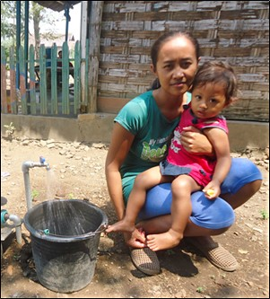 New piped water connection for Indonesian mother and child.