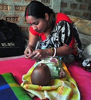 A community health worker assesses an infant