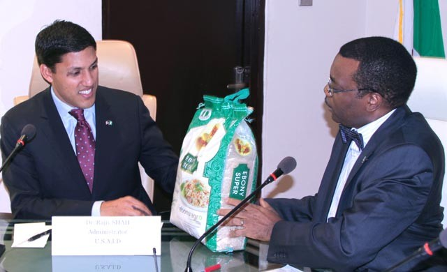 Dr. Akinwumi Adeshina Minister of Agriculture handing a bag of rice to Administrator Shah.