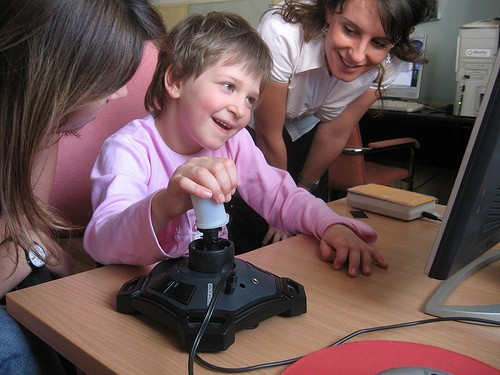 Big-button keyboards, trackballs, touch screens, and joysticks are assistive devices that help students with disabilities partic
