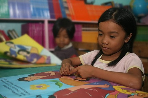 A young girl in the Philippines reads a book provided by a USAID-funded project. Photo Credit: USAID/Philippines
