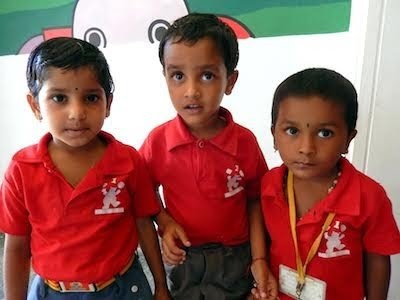Three smiling young children in school uniforms