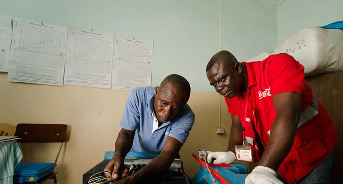Two men work on fixing a refrigerator at a clinic