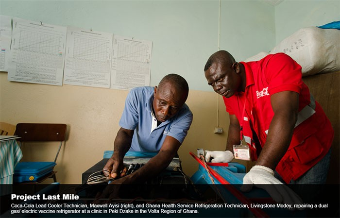 Coca-Cola Lead Cooler Technician, Maxwell Ayisi, and Ghana Health Service Refrigerator Technician repair a vaccine refrigerator.