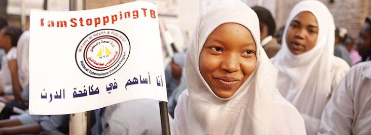 A woman wearing a white head scarf holds up a sign about TB.