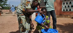 A woman helps a child with handwashing