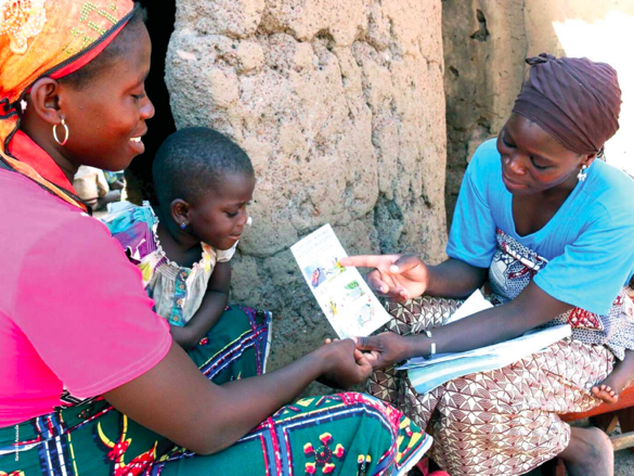 A clinic nurse educates a mother and child