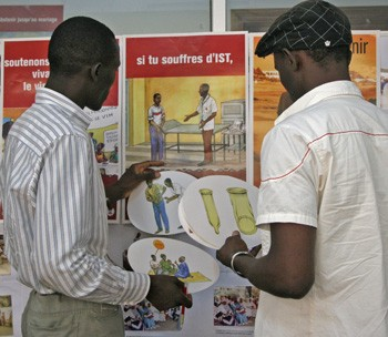 A Senegalese man discusses HIV/AIDS information tools with a representative of a USAID implementing partner.