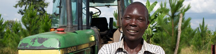 Small farmer Churchill Ojok stands with his tractor. Thanks to a USAID initiative, he is harvesting more efficiently. (Photo cou
