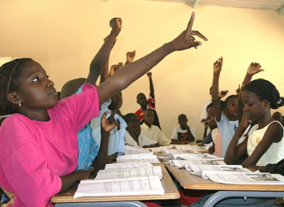 Students raising their hands in class.