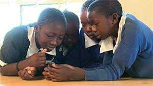 Students in Kenya participate in playing a mobile game that teaches them the importance in making good choices.