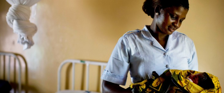 Photo of a midwife in Tanzania holding a baby.