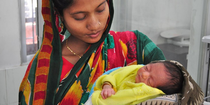 A woman holds her newborn baby