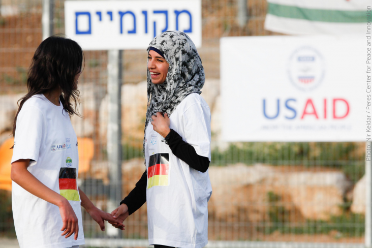 Two girls smiling at each other and holding hands after a USAID-supported day of peacebuilding activities that brings together Arab, Jewish, Israeli, and Palestinian girls in Kiryat Gat, Israel.