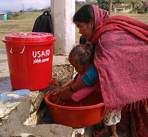 A mother in Nepal washes her child's hands