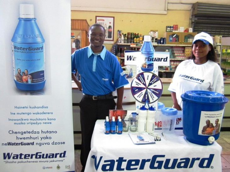In a supermarket in Harare, Zimbabwe, two community outreach members stand at a display promoting WaterGuard