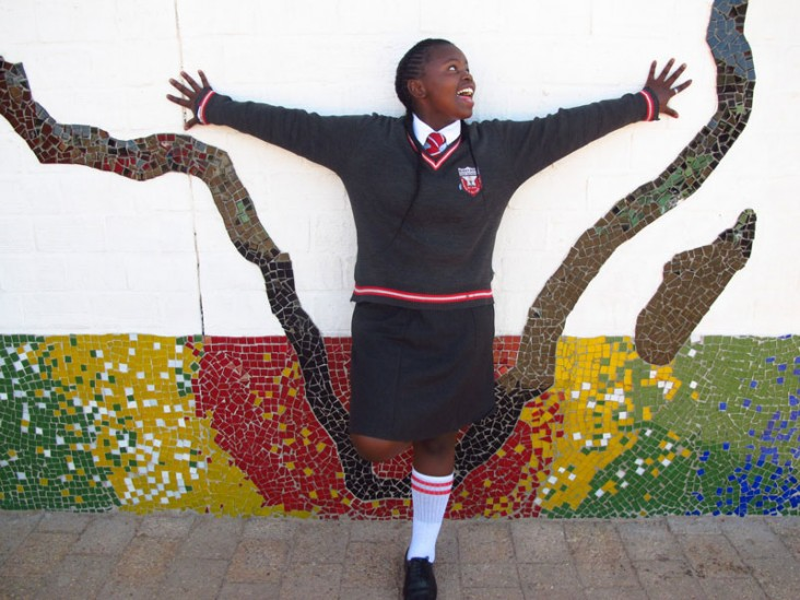 A young girl stands with arms up next to a colorful mural.
