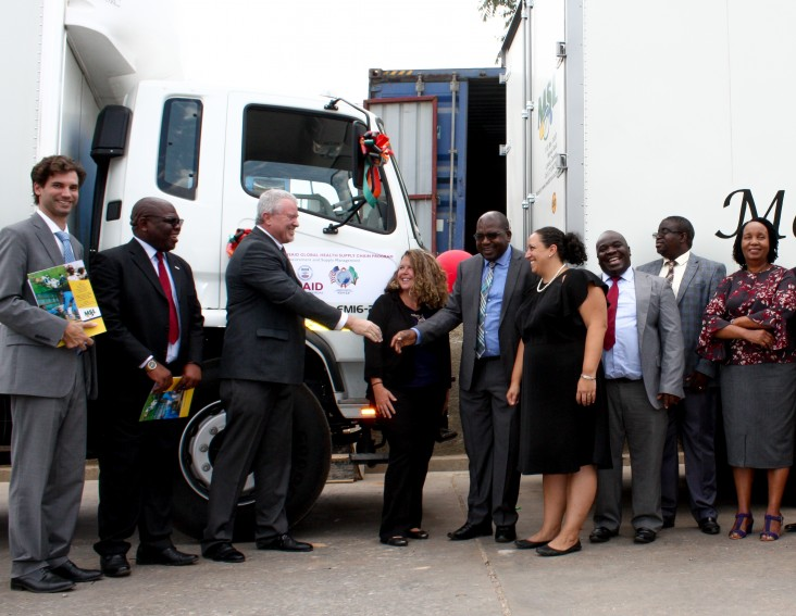 USAID Mission shakes hands with Zambia's Minister of Health during the delivery of 12 vehicles procured to help expand Zambia's medical network.