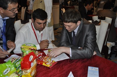 Afghan businessman negotiates with a Kazakh businessman at the B2B event in Kabul.