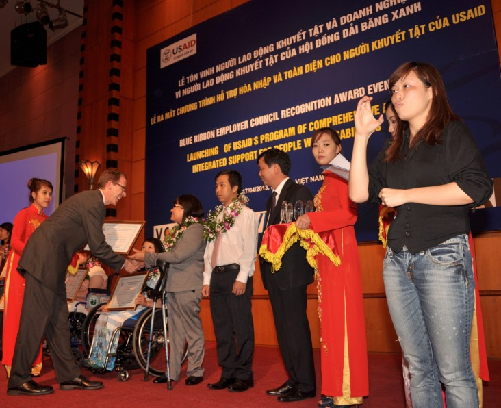 USAID Mission Director Joakim Parker awards employees with disabilities.