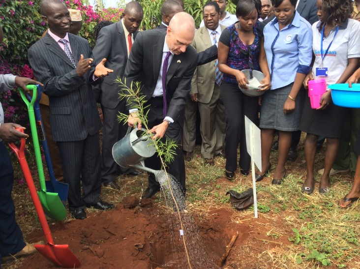 U.S. Ambassador waters a young tree seedling.