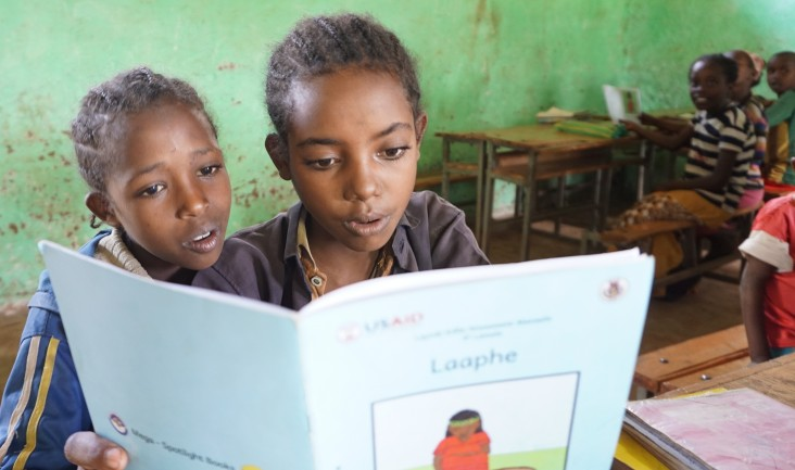 Two girls in a second grade class at the Soyama Primary School practice reading with one of the new supplementary books.