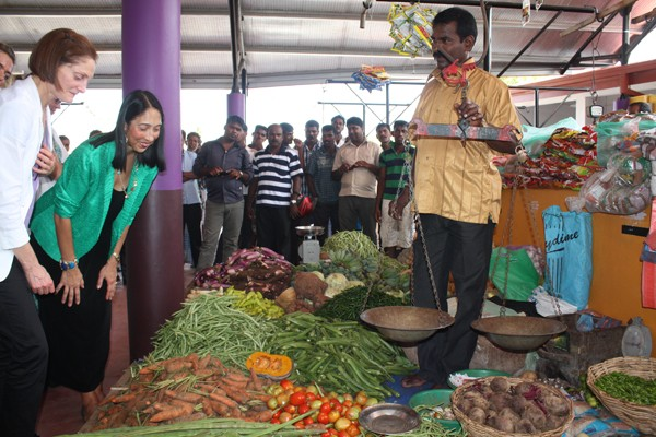 Ambassador Sison and USAID Mission Director Carlin speak to a vegetable vendor during the public market opening in Mullaitivu