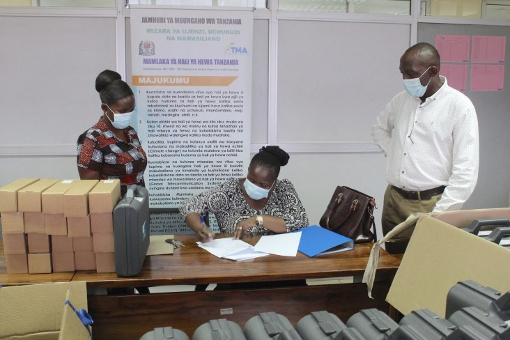 """TMA's Manager for Environment & Research Ms. Sarah Osima signs off on the official handover agrometeorological supplies with FAO's National Project Coordinator Mr. Diomedes Kalisa (right) and In Country Coordinator Ms. Rebecca Mwasyoke of Washington State University International Development Office (left). Since 2015, USAID has funded the """"Building Capacity for Resilient Food Security Project,"""" which provides technical assistance and funding to TMA."""