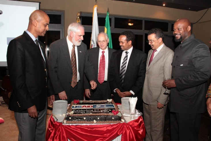 Thomas Staal, Donald Booth, and Ethiopian officials stand around USAID cake