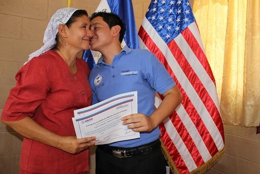 Nain, one of the program beneficiaries, kisses his mother after the graduation