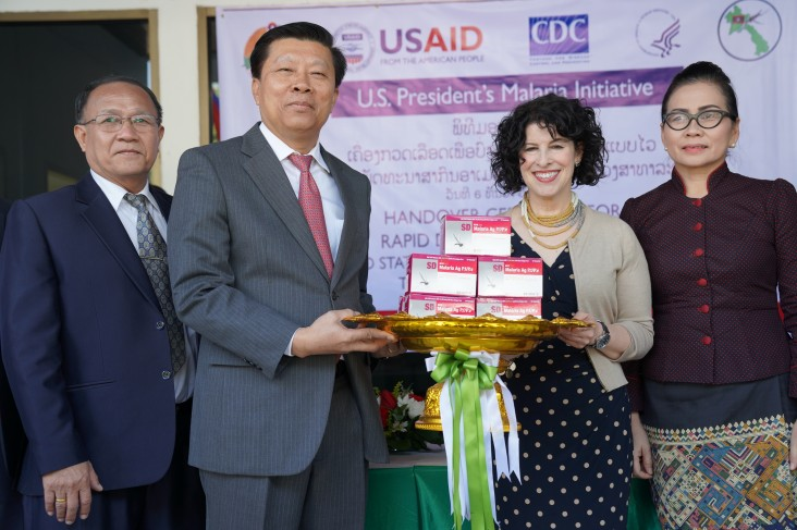 Dr. Phouthone Muoangpak (center left), Vice Minister of Health, receives 100,000 rapid diagnostic test kits from U.S. Ambassador to Laos Rena Bitter (center right) at a handover ceremony in Vientiane on December 6.
