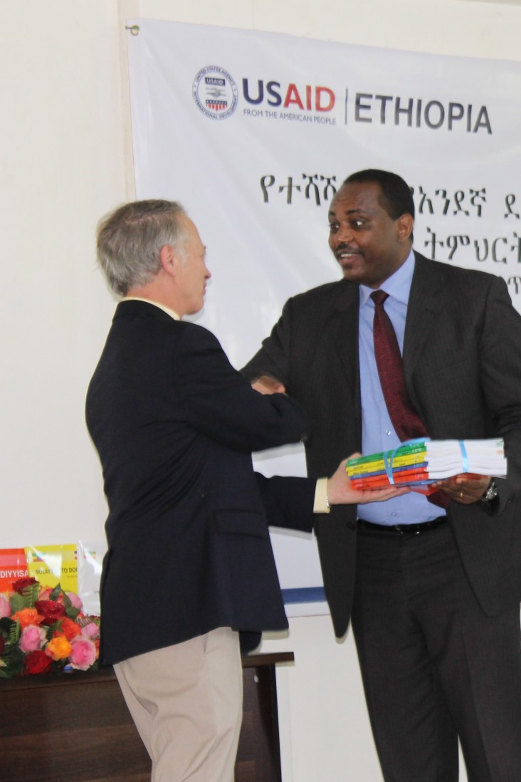 USAID Ethiopia Mission Director Dennis Weller (left) presents some of the new mother tongue reading materials to Minister of Edu