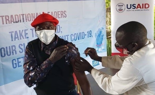 """As part of the Zambia Ministry of Health """"Take the Lead, Roll Up Your Sleeve"""" initiative, with USAID DISCOVER-Health support, an Induna (traditional leader) in Zambia's Western Province receives the COVID-19 vaccine and encourages community members to do the same."""