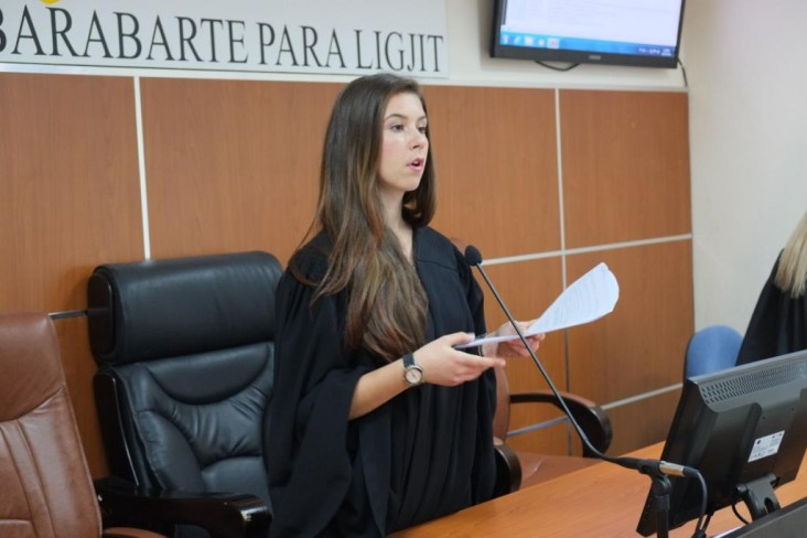 A high school student dressed in a judge's robe participates in a 'mock trial on domestic violence'