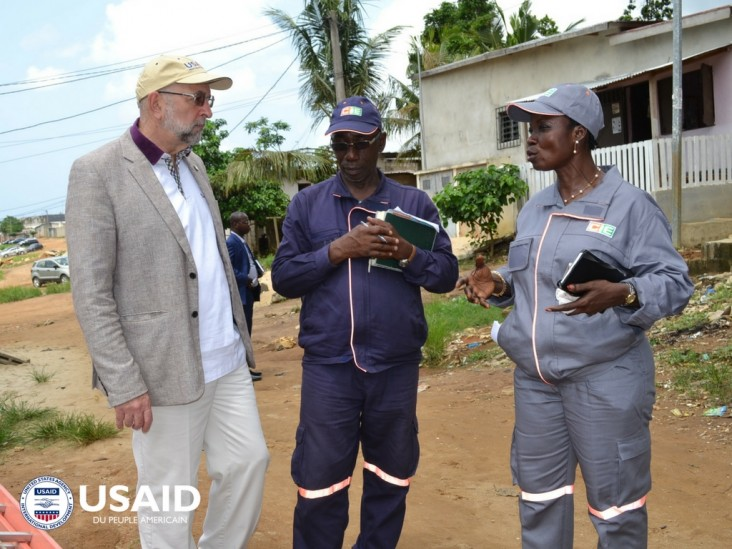 Agents from the power company on the field with former USAID Mission Director
